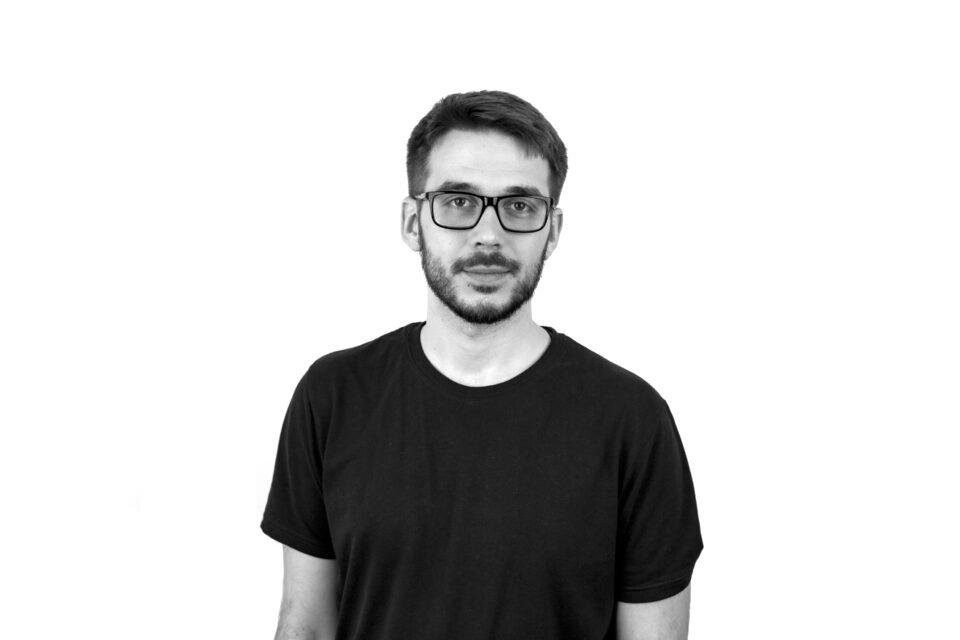Portret młodego mężczyzny w okularach, z brodą, w czarnym t-shircie