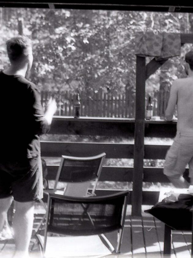 Czarno-biała fotografia. Obraz z Widok na ganek z wnętrza domku letniskowego. Na ganku dwóch mężczyzn oraz rozłożone leżaki