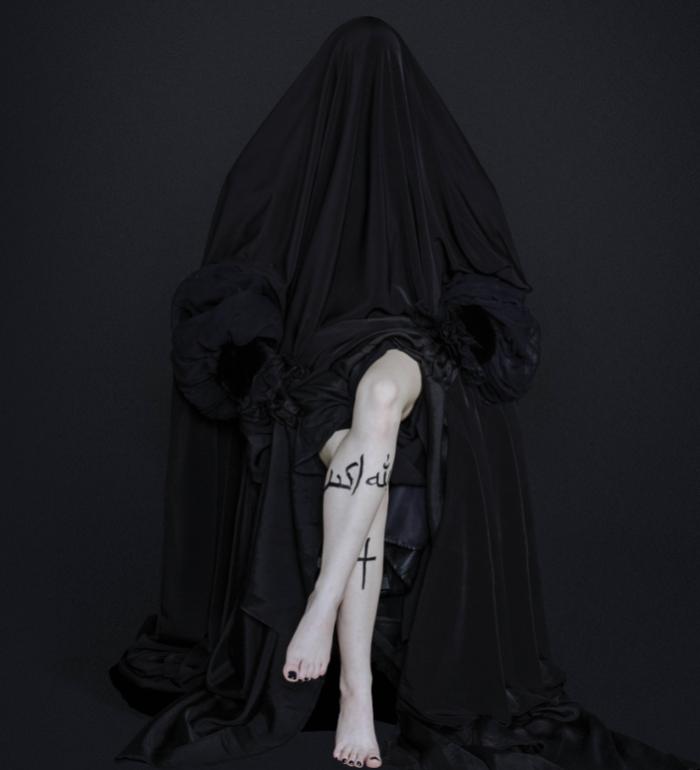 Plakat spektaklu. Fotografia przedstawia siedząca kobietę zakrytą do pasa czarnym materiałem. widać tylko nogi założone na siebie lewa na prawą. Na prawej nodze namalowany krzyż, na lewej napis islam