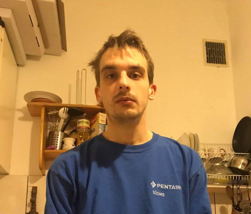 Fotografia artysty. Młody mężczyzna w niebieskim dresie.