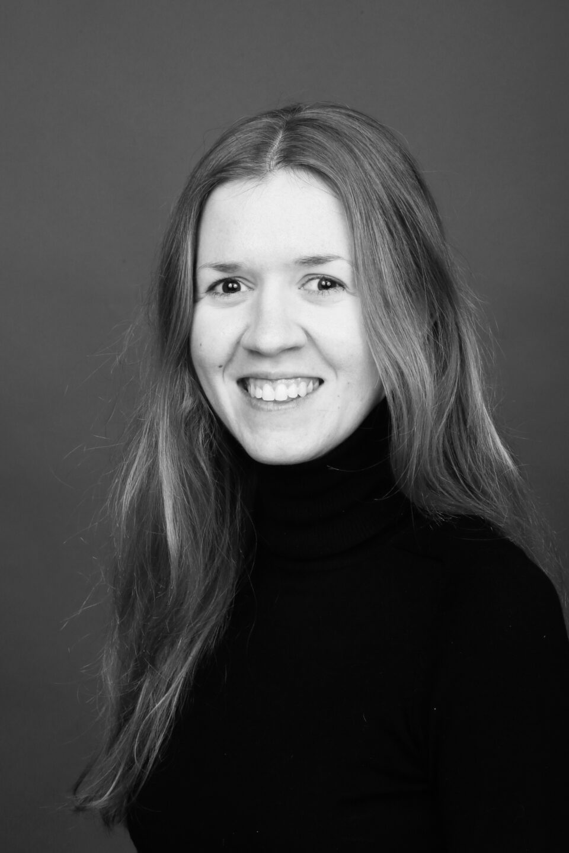 fotografia portretowa przedstawiająca Zofię Gustowską. Zdjęcie czarno-białe. Młoda kobieta z długimi jasnymi włosami patrząca w kierunku obiektywu