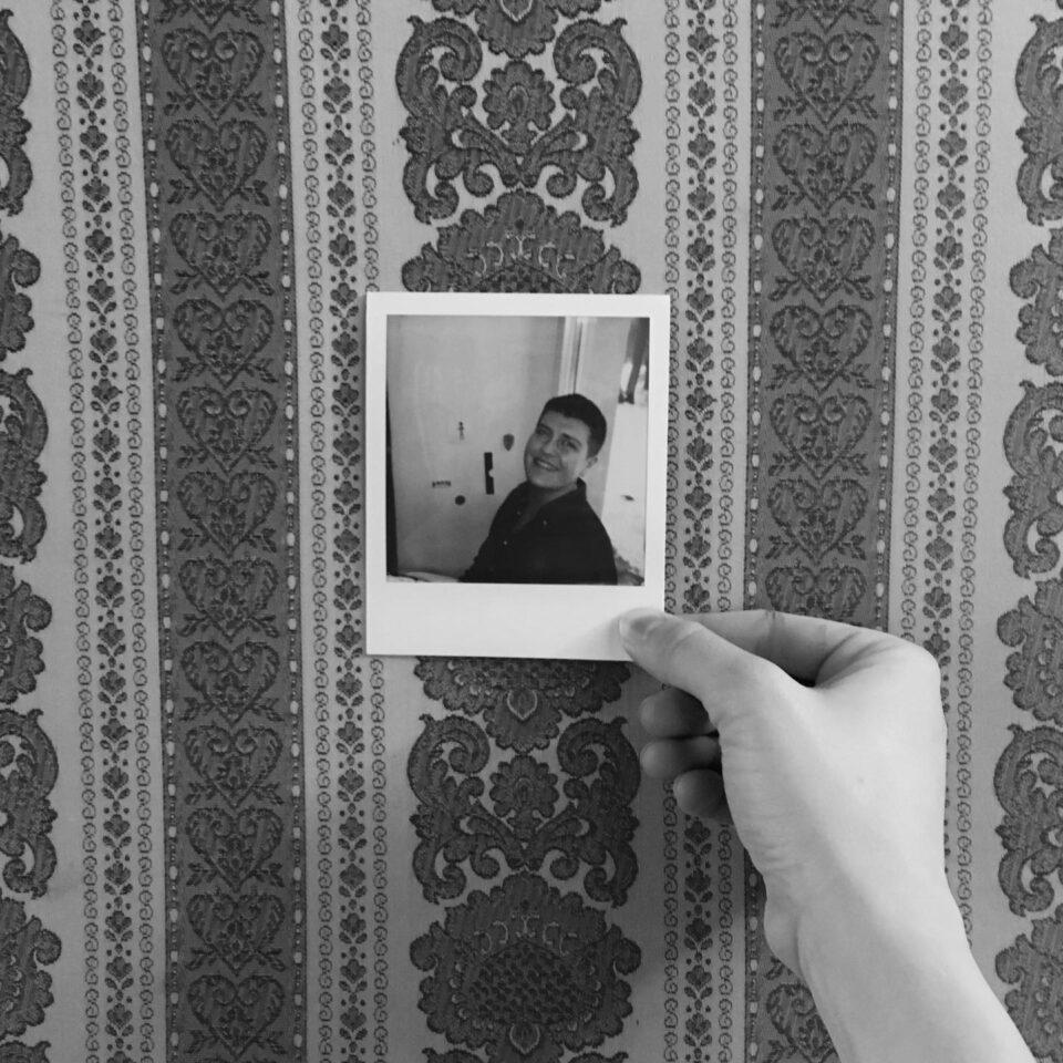 Na obrazku na tle wzorzystej tapety widać rękę trzymającą polaroidowy portret młodego mężczyzny.