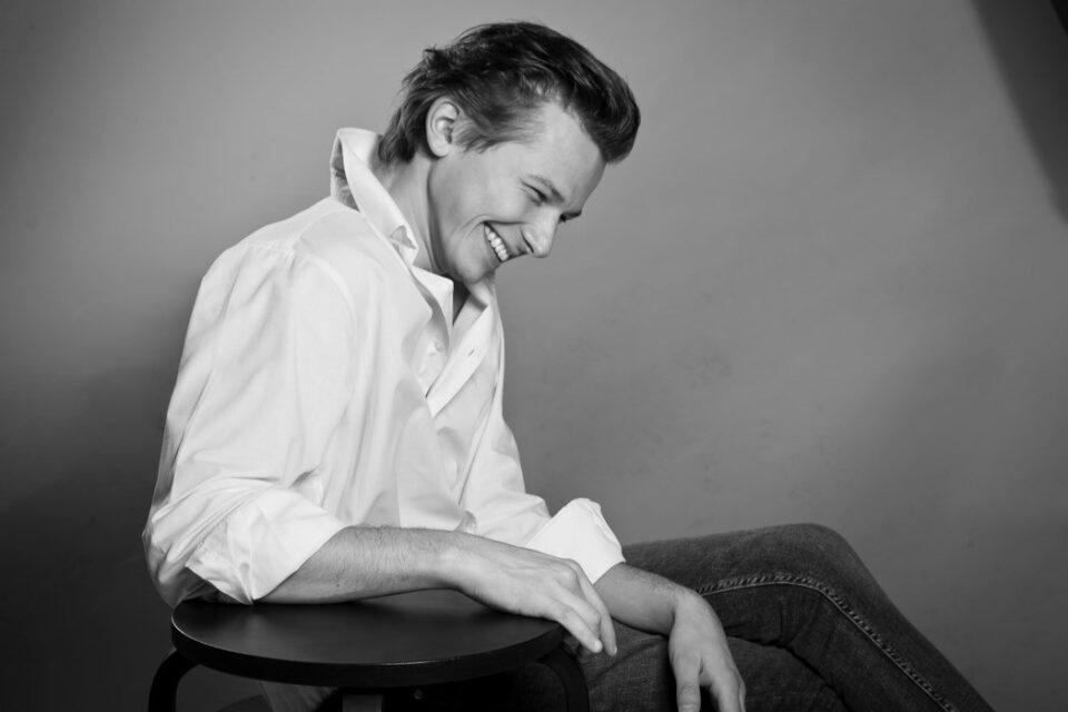 Fotografia artysty. Śmiejący się młody mężczyzna w białej koszuli z postawionym kołnierzykiem. Fotografia czarno biała, zdjęcie z profilu.