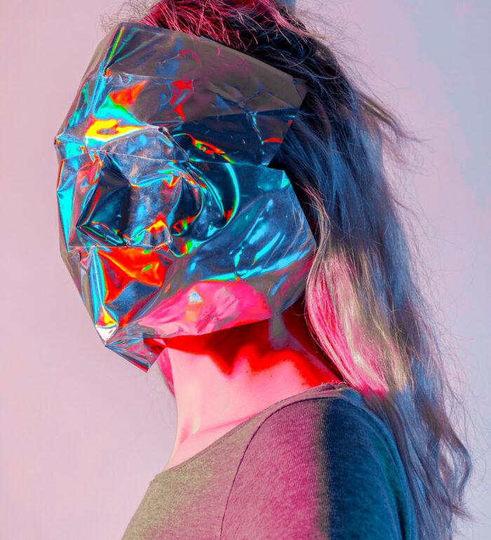 Obrazek przedstawia kobietę stojącą bokiem. Na twarzy ma folię aluminiową.