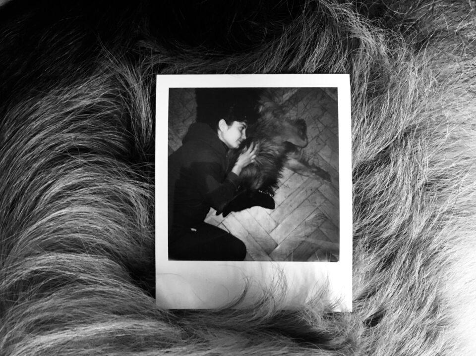 Czarno-białe zdjęcie, na którym polaroidowy portret dziewczyny przytulającej psa położono wśród sierści.