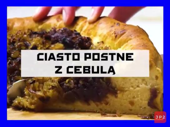"""Obrazek z napisem """"ciasto postne z cebulą"""", przedstawiający jasne ciasto z usmażoną cebulą na wierzchu przytrzymywane dłonią w trakcie krojenia."""