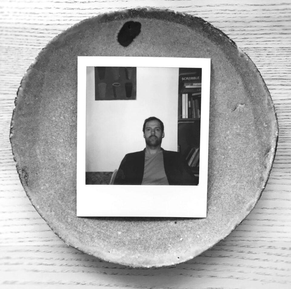 Na okrągłej tacy leży polaroidowy portret młodego mężczyzny w pomieszczeniu na tle białej ściany.