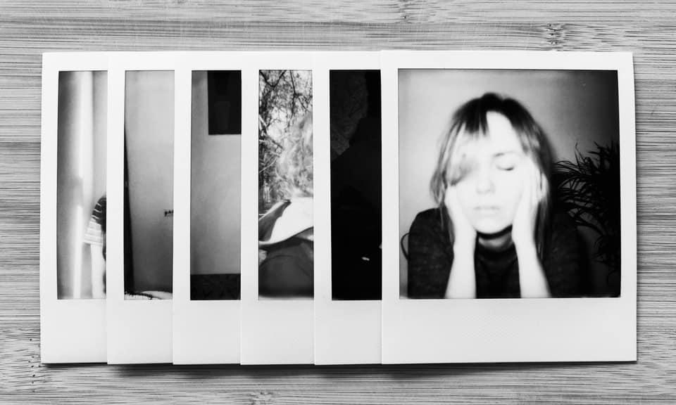 Na blacie kilka czarno-białych portretów polaroidowych, ułożone są jeden na drugim tak, że widać tylko brzeg każdej fotografii a w całości jedynie portret, który leży na wierzchu.