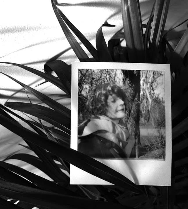Polaroidowy portret młodej kobiety umieszczony wśród liści